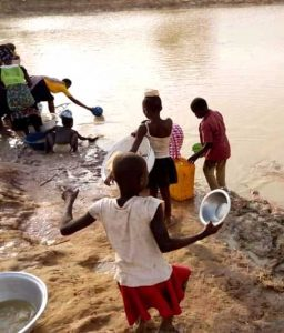 Villagers gather water at muddy river